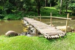 Старый деревянный мост над потоком с зеленой лужайкой Стоковые Изображения RF