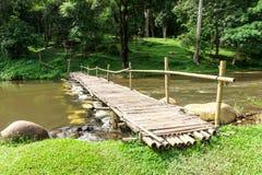 Старый деревянный мост над потоком с зеленой лужайкой Стоковое фото RF