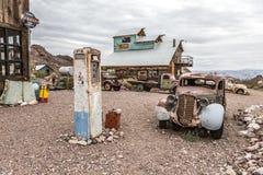 Старый деревянный дом и ржавый старый насос для подачи топлива в призраке Нельсона Невады Стоковая Фотография RF
