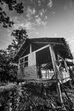 Старый деревянный покинутый коттедж против неба Стоковые Фотографии RF