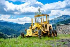 Старый желтый грейдер на гористом строительстве дорог Стоковые Фотографии RF