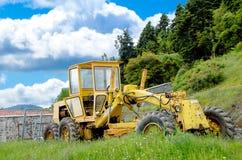 Старый желтый грейдер на гористом строительстве дорог Стоковые Фото