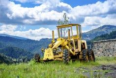 Старый желтый грейдер на гористом строительстве дорог Стоковое фото RF
