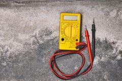 Старый желтый multi метр на пылевоздушной предпосылке цемента стоковое фото rf