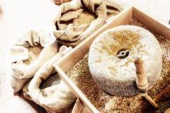 Старый жернов с зернами пшеницы Стоковые Изображения
