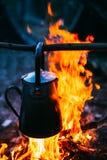 Старый железный чайник лагеря кипит воду на огне в огне пламени леса ярком Стоковое Фото