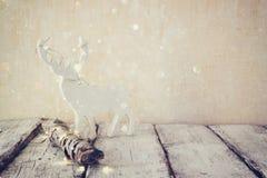 Старый журнал дерева с fairy светами и северным оленем рождества на деревянном столе Селективный фокус верхний слой яркого блеска Стоковые Изображения RF