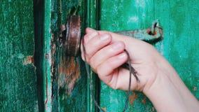 Старый замок утюга года сбора винограда на двери при зеленая слезли краска, который Женская рука раскрывает и закрывает замок сток-видео
