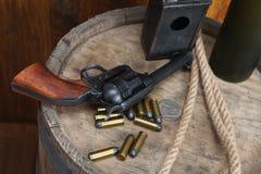 Старый западный револьвер с патронами и серебряным долларом стоковые фото