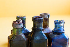 Старый дизайн разливает конец-вверх по бутылкам Красочный пакостный стеклянный комплект flacon Мягкая желтая предпосылка, малая г Стоковое Изображение RF