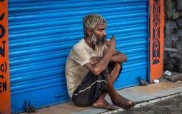 Старый индийский попрошайка сидит перед закрытым магазином и имеет чашку чая утра на дороге в южном Kolkata, западной Бенгалии, И стоковое фото