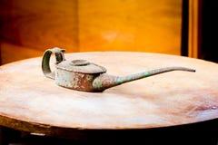 Старый используемый ржавый oilcan на круглом столе Длинный нос, грязное тело стоковое изображение