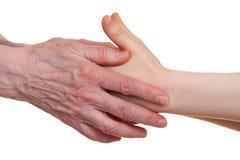 Старый и детеныш держа руки одина другого Стоковое Изображение