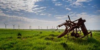 Старый и новая технология - ветротурбины и покинутый плуг Стоковые Изображения