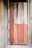 Старый и основной красный цвет покрасил деревянную дверь старого традиционного деревянного тайского дома Стоковые Фотографии RF