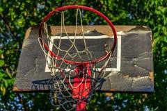 Старый и поврежденный обруч баскетбола с клеткой, деревом и домом в Стоковые Изображения RF