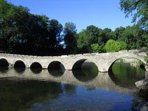 Старый каменный мост на переходе через реку. Стоковая Фотография RF