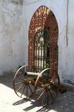 Старый карамболь около чугунного строба Стоковая Фотография