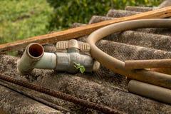 Старый клапан PVC с пластиковым шлангом трубы воды на грязной рифленой крыше - Moldy конкретной текстуре стоковое изображение