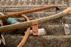 Старый клапан PVC с пластиковым шлангом трубы воды на грязной рифленой крыше - Moldy конкретной текстуре стоковые изображения