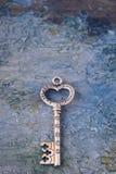 Старый ключ изолированный на конкретной предпосылке с символами влюбленности, утехи, приятельства, везения стоковое изображение rf