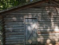 Старый коричневый и серый сарай фермы с заржаветым колесом на внешней стене в лесе стоковое фото rf