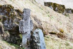 Старый крестовидный камень покрытый с зеленым мхом и сухой травой против времени стены древней крепости весной стоковая фотография rf