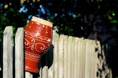 Старый кувшин глины на загородке Стоковая Фотография