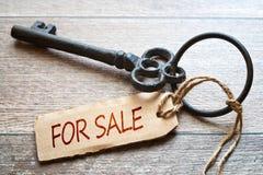 Старый ключ с бумажным ярлыком - для продажи текстом - на деревянной предпосылке имущество принципиальной схемы реальное Стоковые Изображения RF
