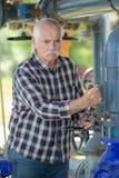 Старый механик работает на токарном станке Стоковое Фото
