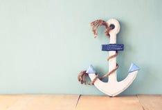 Старый морской анкер на деревянном столе над деревянной предпосылкой aqua Стоковая Фотография