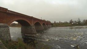Старый мост кирпича через реку Venta в городе видео timelapse Kuldiga Латвии сток-видео