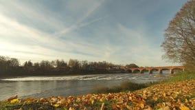 Старый мост кирпича через реку Venta в городе видео timelapse Kuldiga Латвии видеоматериал