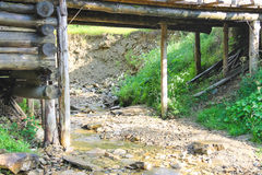 Старый мост над потоком леса в горячем летнем дне Стоковые Изображения RF