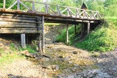 Старый мост над потоком леса в летнем дне Стоковые Изображения RF