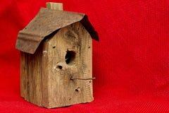 Старый несенный Birdhouse - изолированный на красной ткани мешковины Стоковые Фото