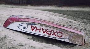 Старый переворачиванный цвет шлюпки красный лежит на береге высушенного озера Надпись на стороне ПРЕДОХРАНЕНИЯ ОТ шлюпки Стоковое Фото