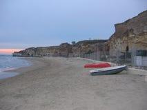 Старый пляж Anzio к заходу солнца с некоторыми шлюпками на песке, Италия Стоковое Изображение RF