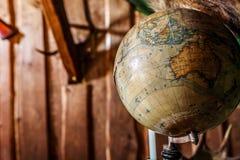 Старый поврежденный глобус против деревянной стены. Стоковая Фотография