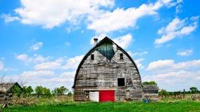 Старый покинутый амбар сидит распадаться на пустой ферме Стоковые Изображения RF