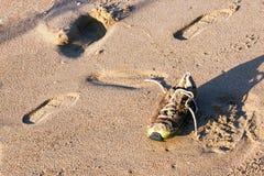 Старый покинутый влажный пакостный ботинок на песке пляжа Стоковая Фотография RF