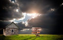 Старый получившийся отказ дом в поле около перерастанной дороги стоковое фото