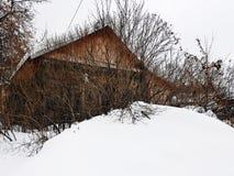 Старый получившийся отказ дом со сломленным окном на предпосылке снега в зиме стоковое фото rf