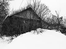 Старый получившийся отказ дом со сломленным окном на предпосылке снега в зиме стоковые фото