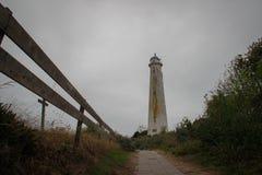 Старый получившийся отказ маяк привел песочной дорогой ограженной  Пасмурный дождливый день на острове Terschelling стоковые фото