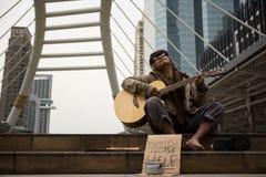 Старый попрошайка поет и играет гитару Стоковое фото RF