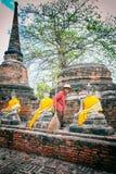 Старый привратник работника очищает зону вокруг статуй Wat Yai Chaimongkhon Стоковые Фото