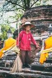Старый привратник работника очищает зону вокруг статуй Wat Yai Chaimongkhon Стоковое Изображение