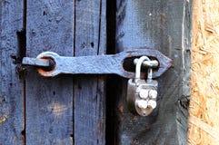 Старый прикрепленный на петлях замок утюга на двери или воротах стоковые фотографии rf