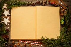 Старый пробел раскрыл книгу с украшениями рождества вокруг на древесине